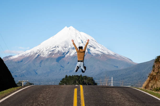 Person in victory success winning pose in front of mountain peak. stock photo