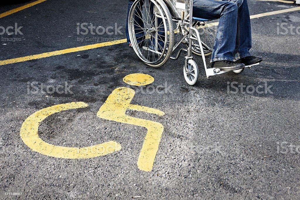 Person im Rollstuhl neben ein Eingeschränktes Parkverbot – Foto