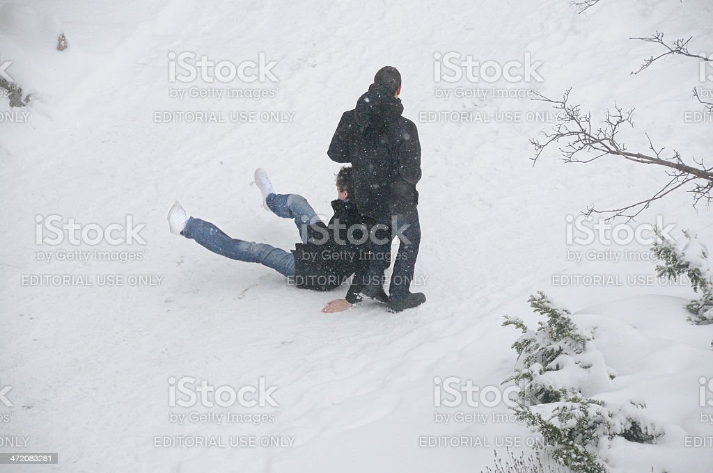 Person in winter clothes slipping on snow covered sidewalk royalty-free stock photo