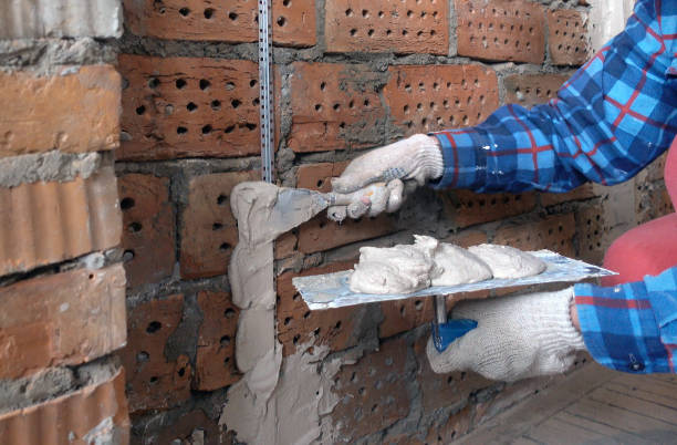 person in work gloves ( hand in the frame) holds a trowel with plaster and attaches construction beacons to a brick wall with a spatula.