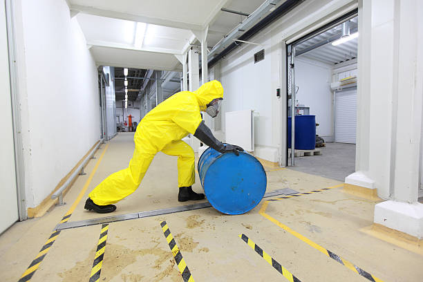 Person in yellow protective gear rolling blue toxic barrel stock photo