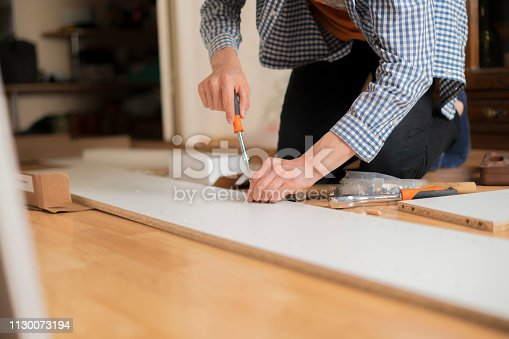 istock person installing new furniture in his accomodation on wooden floor а 1130073194