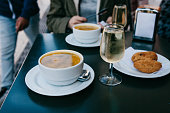 A person is going to eat traditional Portuguese food - soup and patty with a cod called Pastel and drink a glass of white wine in a street cafe.