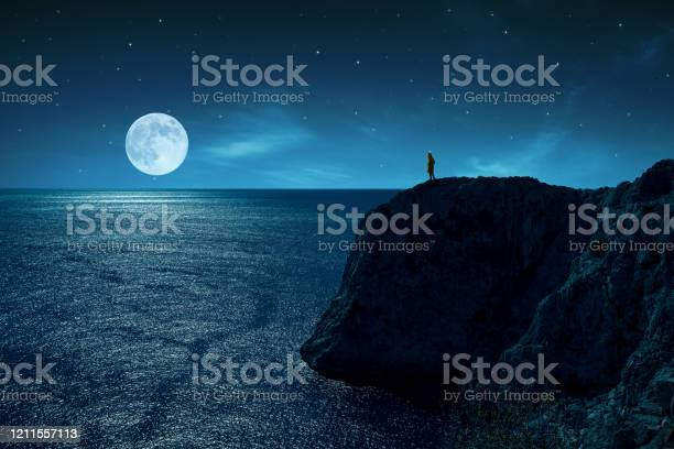 Photo of Person is standing in the edge of a cliff against the sea and full moon, under stars and moon light.