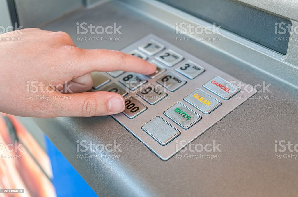 Person is using keypad, entering pin code in ATM machine stock photo