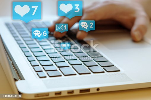 497982910 istock photo Person is using laptop with black keys, Social media and social networking. Marketing concept. Hearts and letterboxes with counters. Marketing and business concept. May be used for illustration. 1168069618