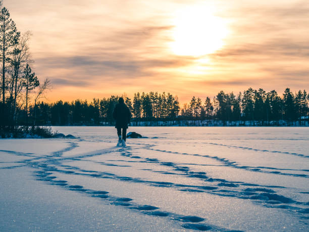 Person is walking on the snowy ice lake in sunset. Winter landscape. stock photo