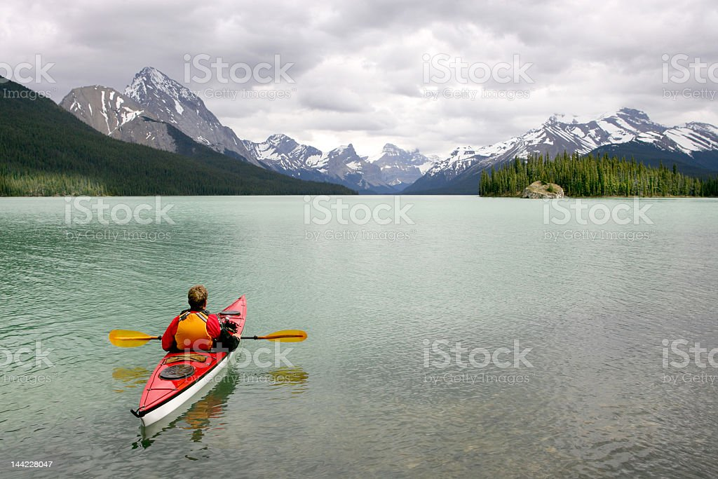 A person kayaking in Banff with mountains in the background stock photo