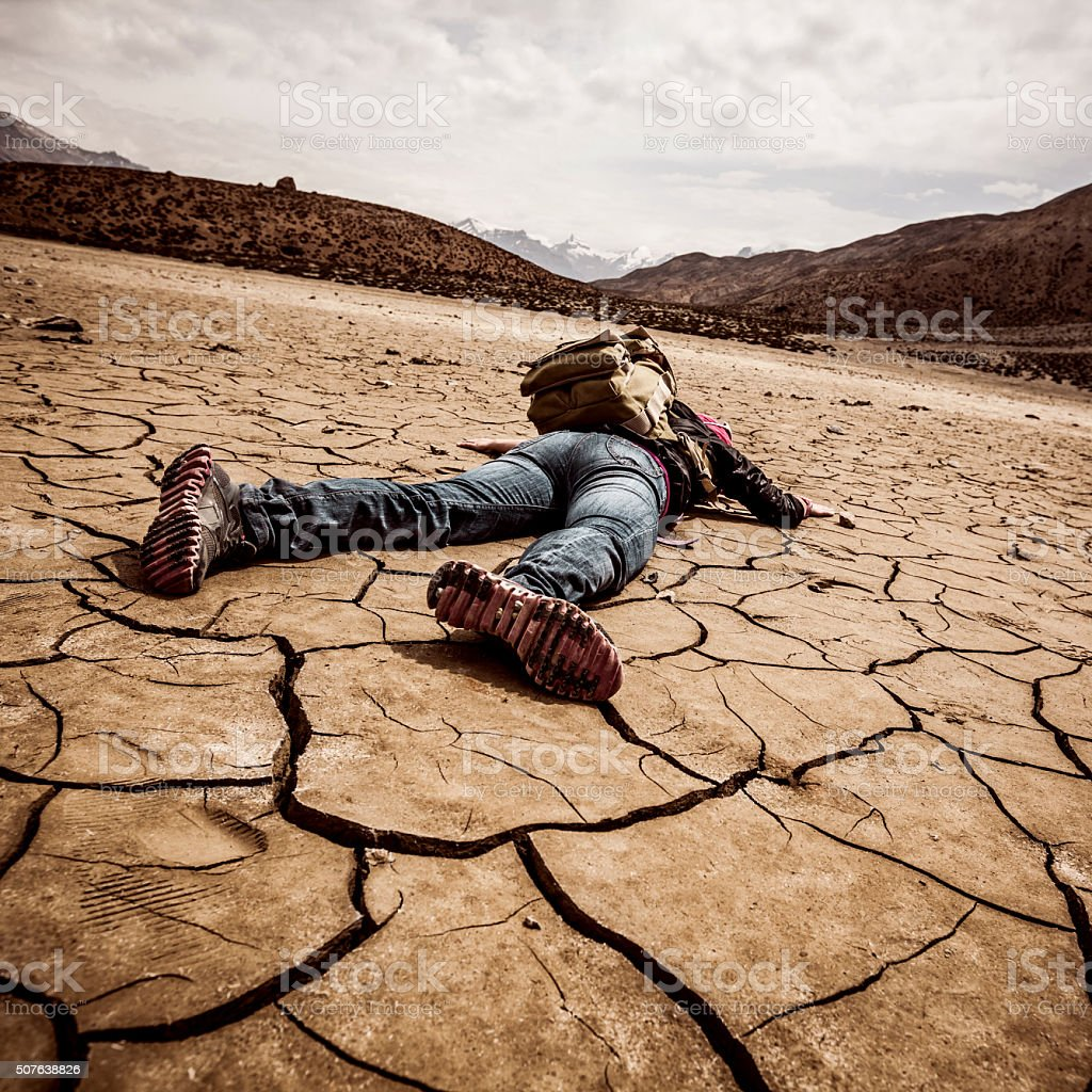 person lays on the dried ground stock photo