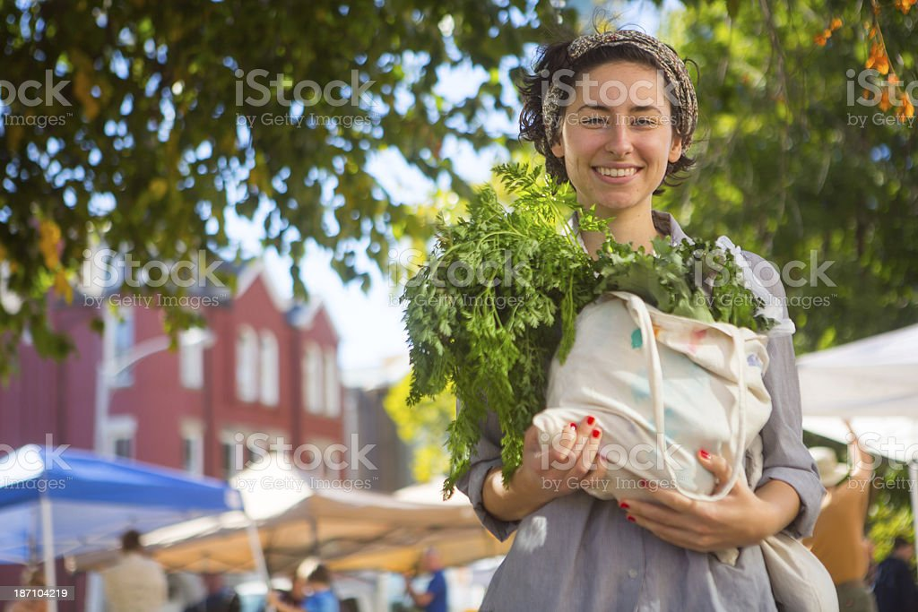 Person leaving farmers market with large bag of vegetables royalty-free stock photo
