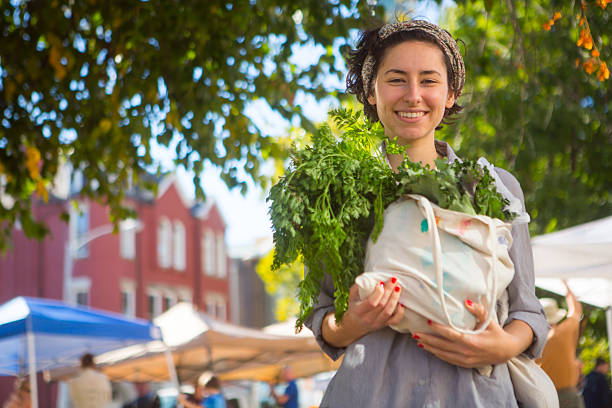 Person leaving farmers market with large bag of vegetables stock photo