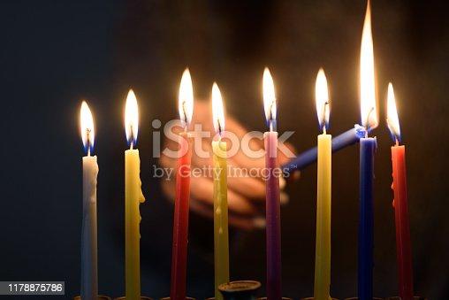 istock A person lighting Hanukkah Candles in a menorah. 1178875786