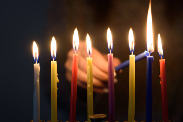 a person lighting hanukkah candles in a menorah. - hanukkah stock pictures, royalty-free photos & images