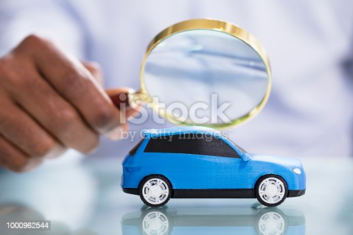 istock Person Looking Blue Car Through Magnifying Glass 1000962544
