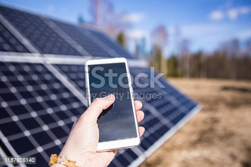 Person looking smartphone screen outdoors on field with solar panels station farm on background. Checking app.