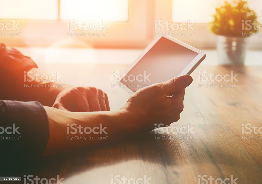 person looking to the digital tablet stock photo
