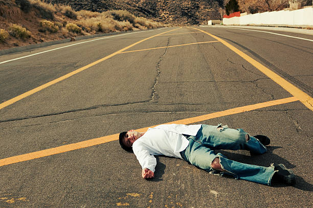 A person lying in the middle of a road  stock photo