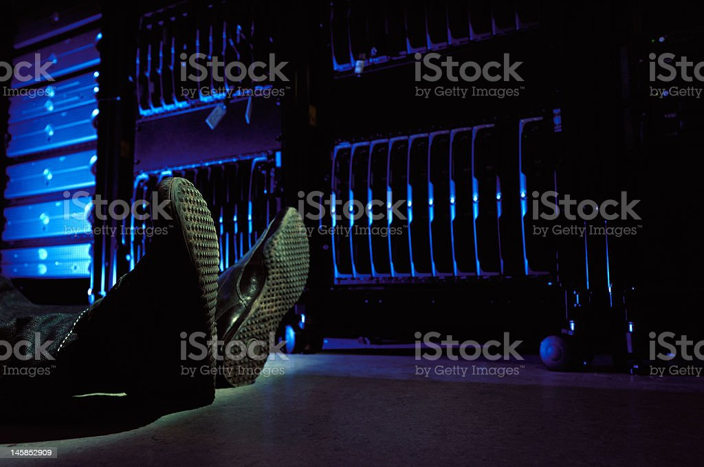 Person lying on the floor in data center stock photo