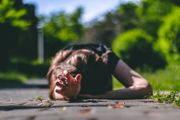 Person lying on the ground with one hand reaching for help stock photo