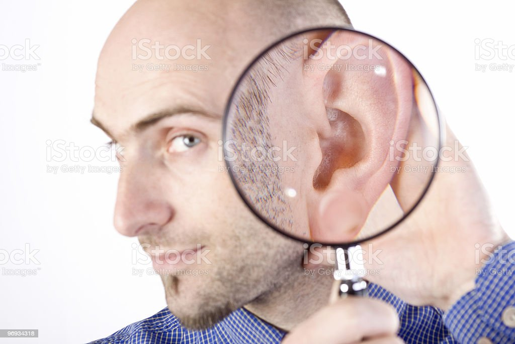 A person magnifying their ear to indicate their listening royalty-free stock photo