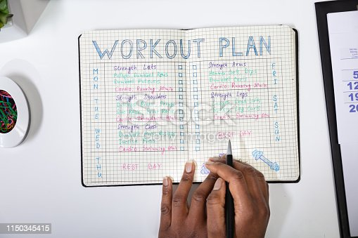 An Elevated View Of A Person Making Note Of Workout Plan On Notebook