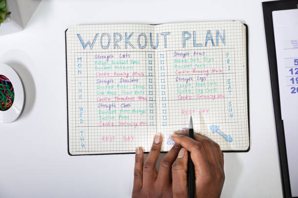Person Making Note Of Workout Plan On Notebook stock photo
