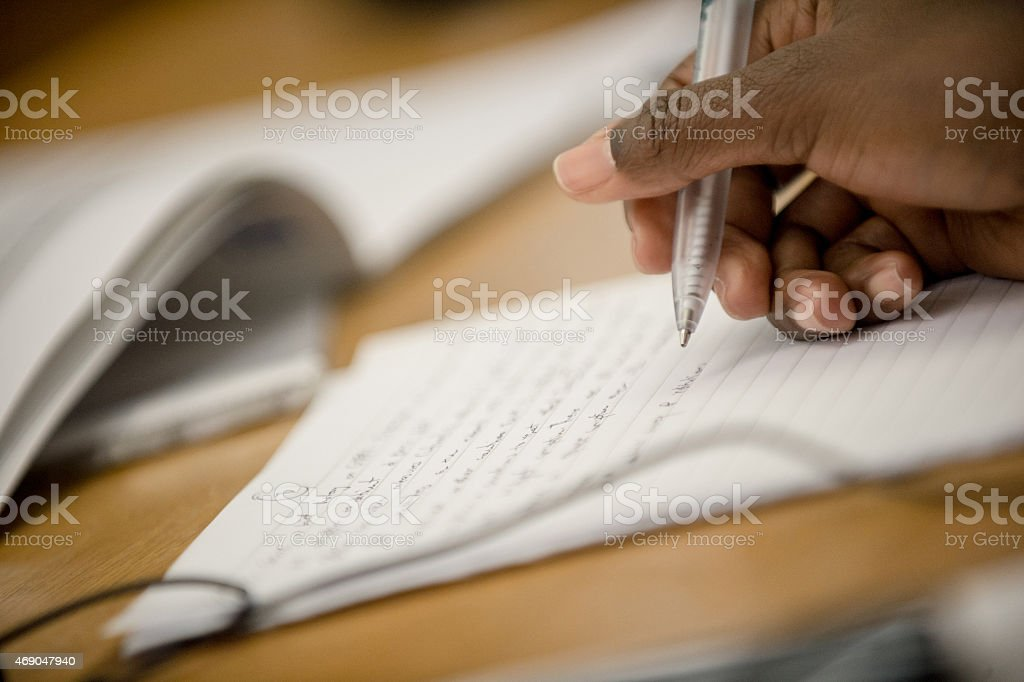 Person making notes on writing paper stock photo
