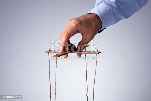 istock Person Manipulating Marionette With String 1050881774