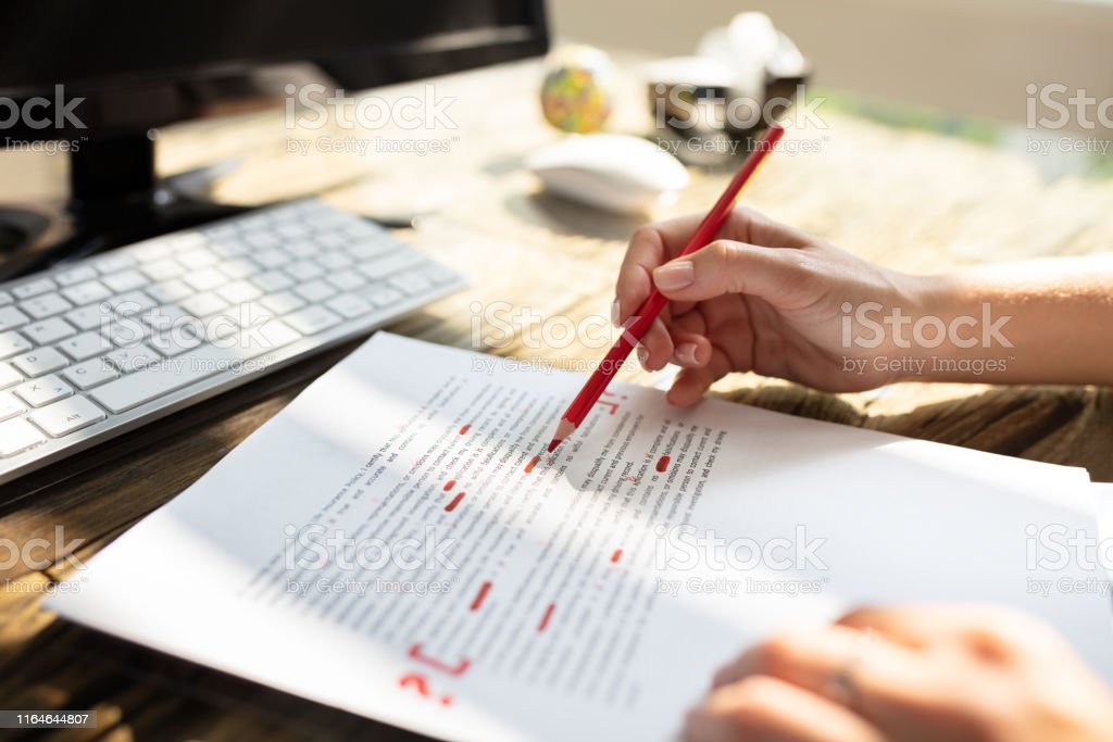 Person Marking Error With Red Marker Close-up Of A Person's Hand Marking Error With Red Marker On Document Accuracy Stock Photo