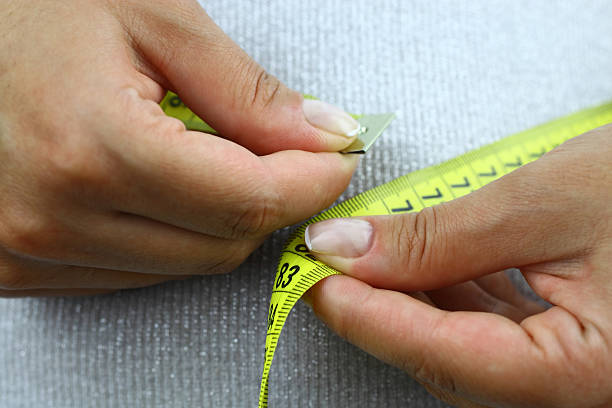 Person measuring their waste line stock photo