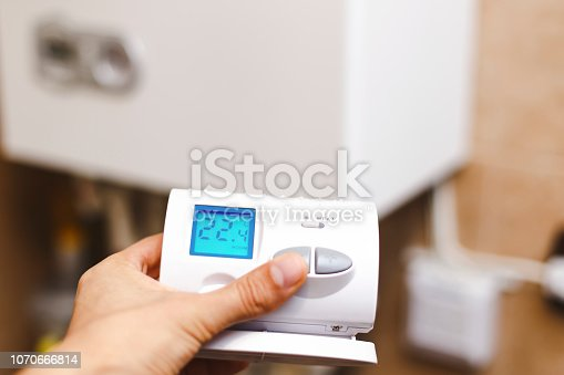 istock Person near central heating controlling the temperature with a radio device. 1070666814