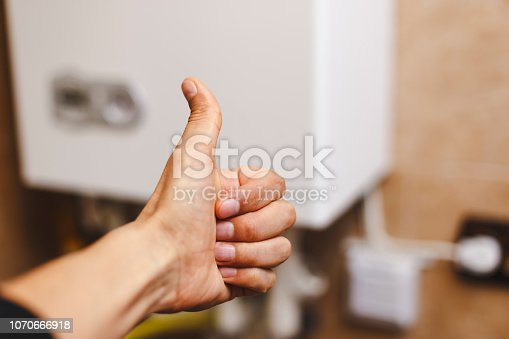 istock Person near central heating with thumb raised in gratitude. 1070666918