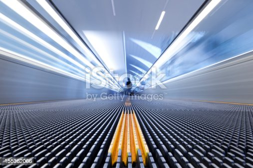 istock Person on a moving escalator with yellow stripes 155362066