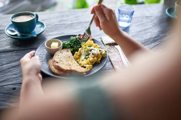 Person on diet eating healthy breakast of scrambled eggs, toast, pan-fried kale and fair-trade coffee stock photo