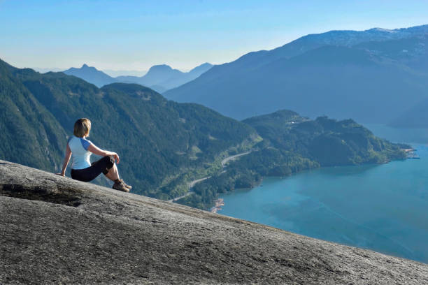 Person on granite cliff enjoying the scenic view of Sea-To-Sky road and ocean bay surrounded with mountains. stock photo