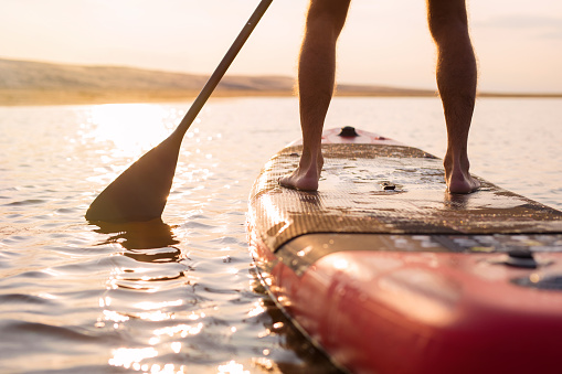 Person on paddle board at sunset