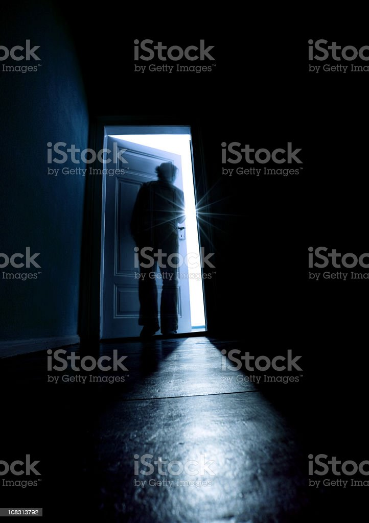 Person opening a door from a dark room into the light stock photo