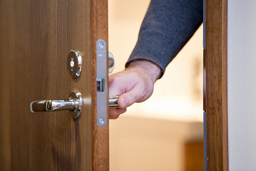 A person opening a wooden door