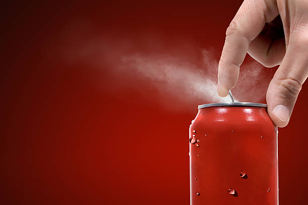 Person opening can of carbonated beverage stock photo