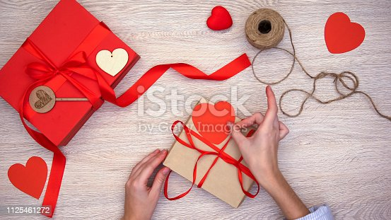 istock Person packing b-day present, putting red paper heart on craftbox Valentines day 1125461272