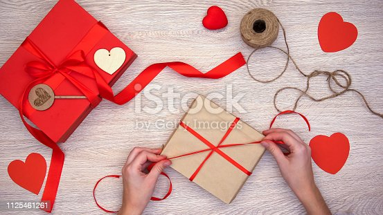1125461272 istock photo Person packing craft Valentines gift box on wooden background, preparation 1125461261