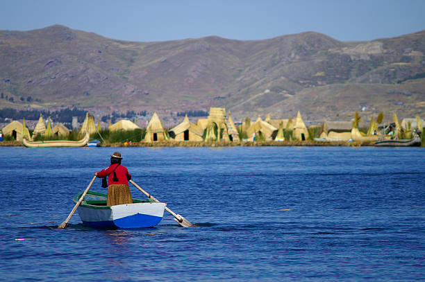person paddling on a small boat at uros islands - 玻利維亞 個照片及圖片檔