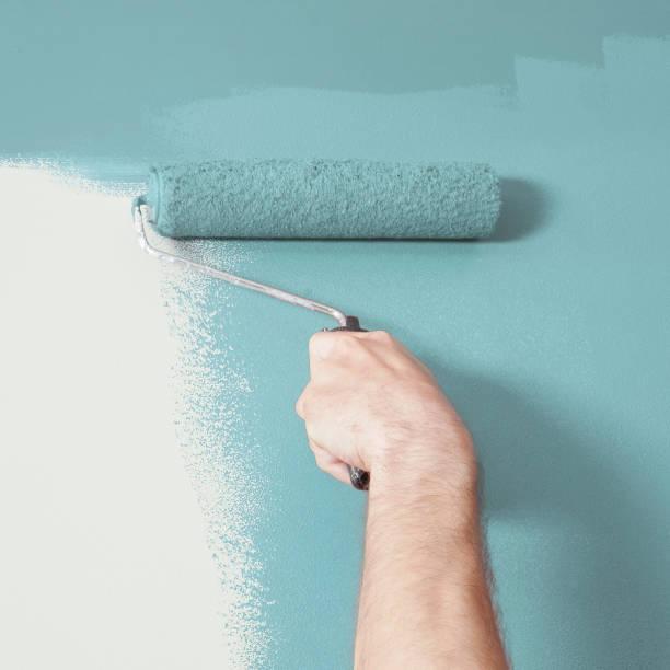 Person, die Malerei einer Wand blaues mit einem Farbroller – Foto