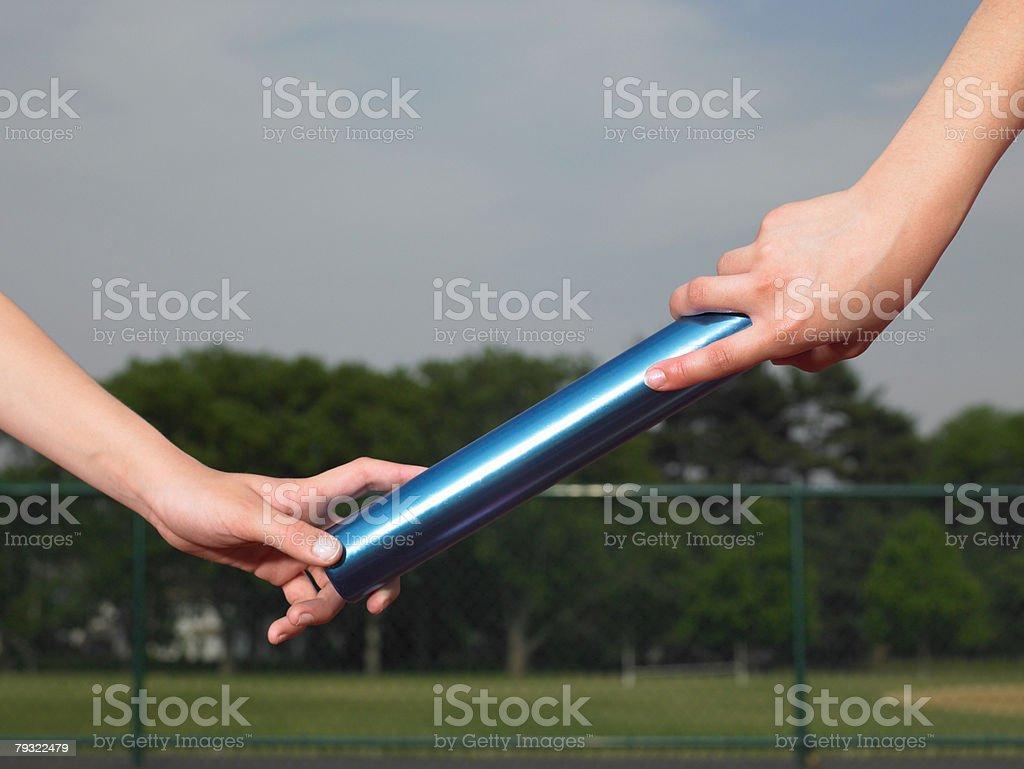 A person passing a baton 免版稅 stock photo