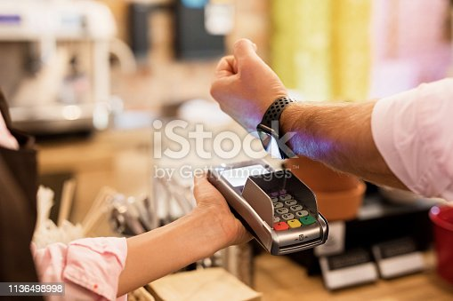 Close-up photo of person paying at cafe with smart watch wirelessly on POS terminal