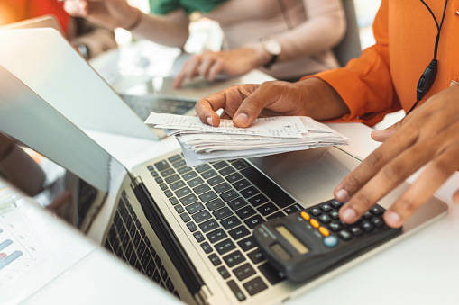 Photo of table full with papers invoices cheque bills, female hands holding receipt calculating company expenses results of incomes, bookkeeper accountant doing paperwork concept