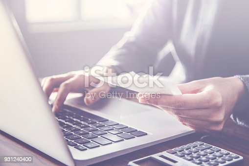 istock Person paying invoice to computer 931240400