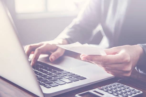 Person paying invoice to computer stock photo