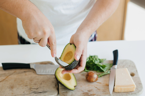 Person peeling perfectly ripe avocado with spoon for sandwich on modern white kitchen. Process of making healthy toasts with avocado, tomato, arugula, cheese. Home cooking concept