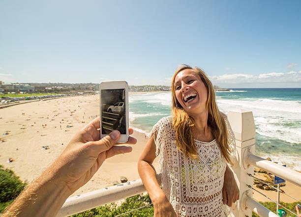 person photographing girl at bondi beach using mobile phone - modefarben sommer 2016 stock-fotos und bilder